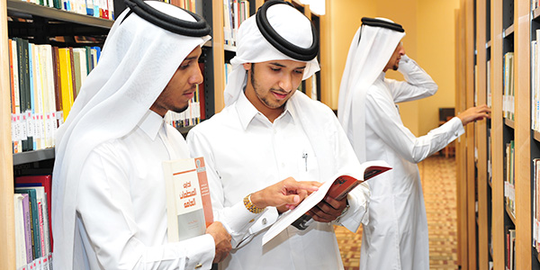 photo of two students reading a book